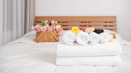 Spa wellness concept with white towels,candle,milk soap,beautiful frangipani  flowers in bamboo wooden basket  on modern white bedroom