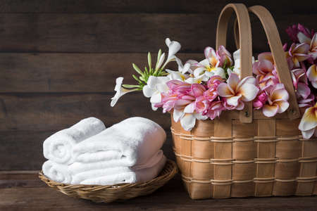 Beautiful frangipani or plumeria flowers in wooden basket and white towels floded on bamboo basket over dark wooden room 版權商用圖片