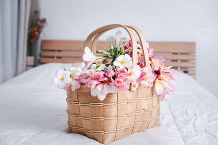 Beautiful frangipani or plumeria flowers in bamboo wooden basket  on modern white bedroom,welcome flower