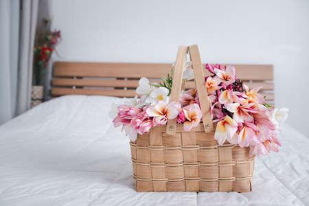 Beautiful frangipani or plumeria flowers in bamboo wooden basket  on modern white bedroom,welcome flower 版權商用圖片 - 157468737