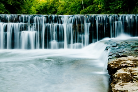 Water flows over an old mill dam