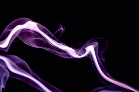 Purple smoke drifts against a black background  Stock Photo