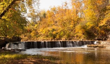 crick: L'acqua scorre su un vecchio mulino diga in autunno Archivio Fotografico