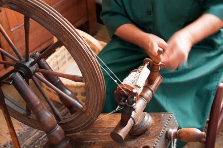 A woman feeds wool into a spinning wheel to make yarn 版權商用圖片