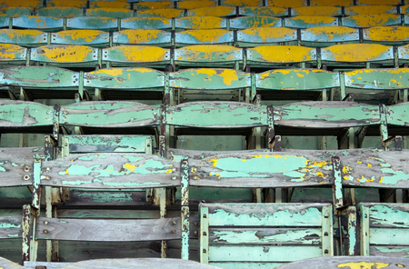 Old painted wooden seats of a stadium grandstand.