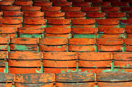 Old orange and green painted seats. Imagens