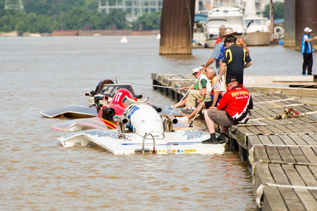 Madison, Indiana  - July 2, 2016:  Boats line up at the dock before a Grand National Hydroplane qualification heat at the Madison Regatta in Madison, Indiana, July 2, 2016.