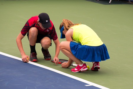 cornet: Mason, Ohio - August 13, 2016: Alize Cornet stops play and is helped by a ball boy to move a bug off the court in a qualifying match at the Western and Southern Open in Mason, Ohio, on August 13, 2016. Editorial