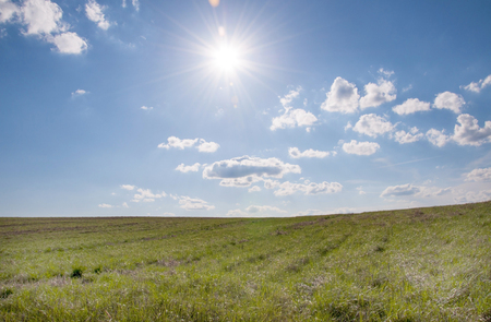 and he shines: The sun shines over a grassy field and clouds int he sky.