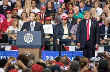 Tampa, Florida – July 31, 2018:  Representative Ron DeSantis addresses a crowd while President Donald Trump watches at a rally in Tampa, Florida, on July 31, 2018.