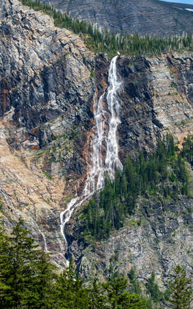 Water falls down mountains in Glacier National Park.