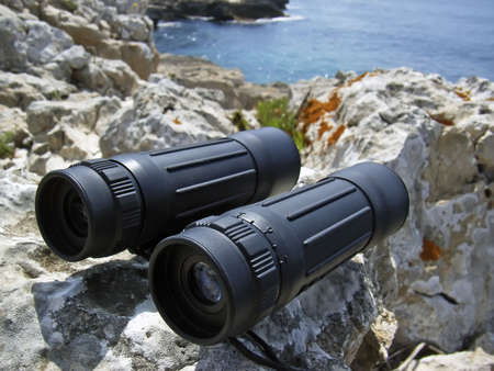 distant: Hand-held binoculars used in exploration for viewing distant objects Stock Photo