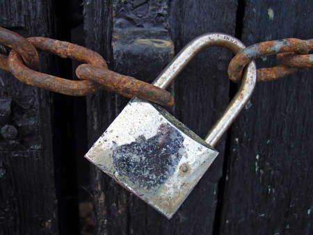hasp: Old Padlock closing a wooden barrier                                                                Stock Photo
