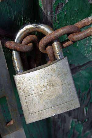 hasp:  Old Padlock with a chain on a closed door