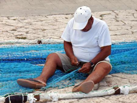 colom: Man repairing the fishing nets on Porto Colom (Majorca - Spain)