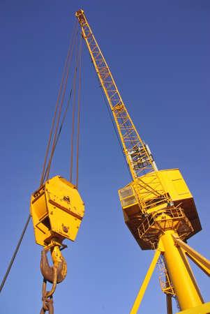 Yellow industrial crane on a cargo dock photo