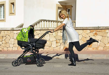 young mother walking with a baby stroller photo