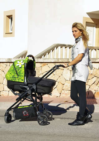 ni�o empujando: joven madre caminaba con un cochecito nuevo dise�o