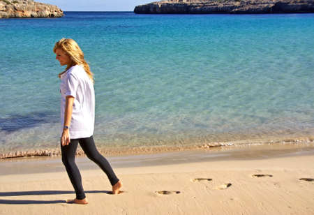 walking alone: joven rubia caminando sola y descalza por la arena de una playa mediterr�nea Foto de archivo