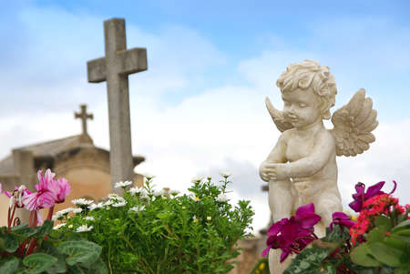 Standbeeld van een engel jongen zich in een begraafplaats Stockfoto