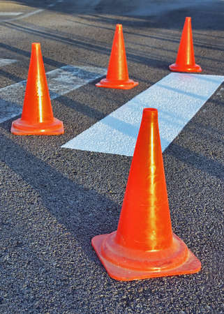 Red Traffic Cones used to inform about a problem on the road pavement  photo