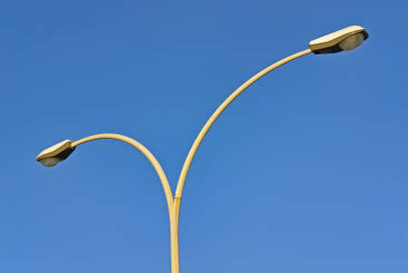 Double headed street lamp over a blue sky background photo