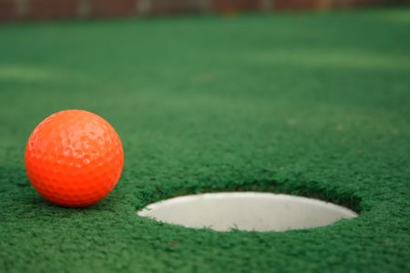mini: A miniature golf ball near the hole