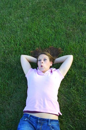 Young woman being silly laying in the grass photo