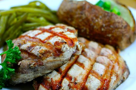 Delicious pork chop meal with a baked potato photo