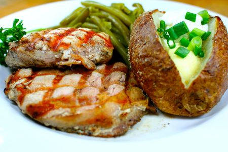 Delicious pork chop meal with a baked potato Stock Photo