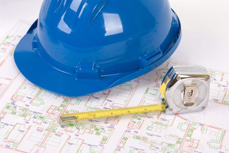 Safety gear, measuring tape and plans - over a white background photo