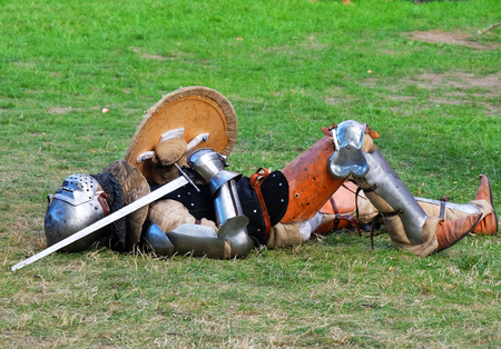 A knight lying on the grass, tired or injured after a fight.