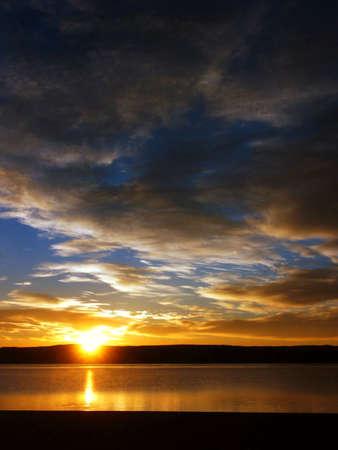 lake beach: Sunrise and clouds on a lake beach with blue sky