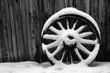 old wood farm wagon: Antique Wagon Wheel with Snow