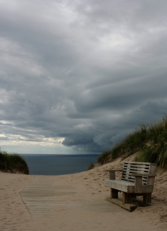 An impending storm rolls over an empty bench along the shoreline in Northern Michigan