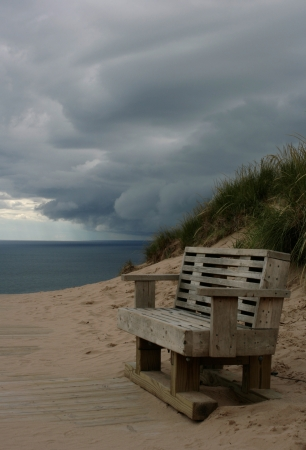 An impending storm rolls over an empty bench on the shoreline in Northern Michigan