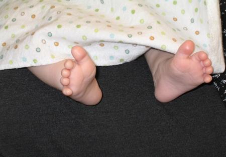 The happy feet of a breast-feeding baby express the pleasure she feels  Stock fotó