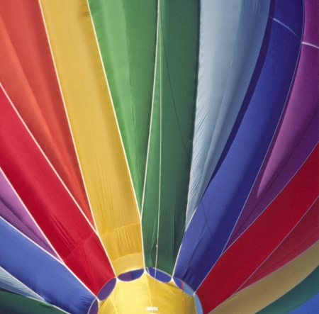 The brightly colored envelope of a hot air balloon paints a rainbow overhead  Stock Photo