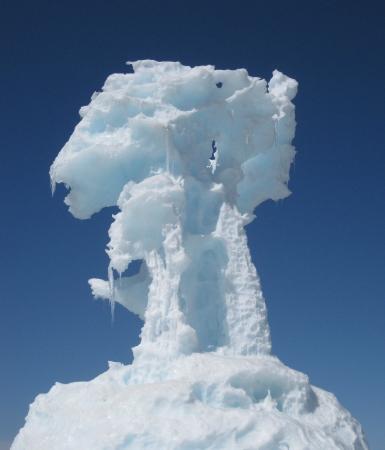 A winter ice column juts into an azure sky