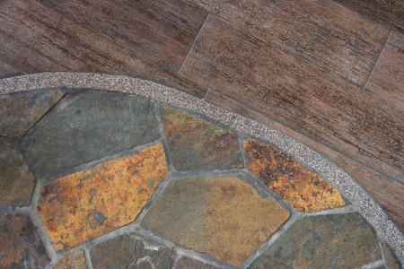 The border between flagstone and old wood flooring create an abstract pattern  Stock Photo