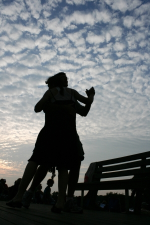A couple dances at dusk at a music festival
