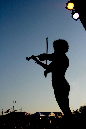 fiddler: A fiddler entertains the audience at a music festival  Stock Photo