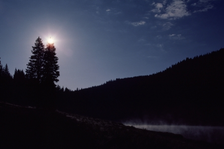 A high mountain sunrise crowns a Colorado forest and lake  Stock Photo