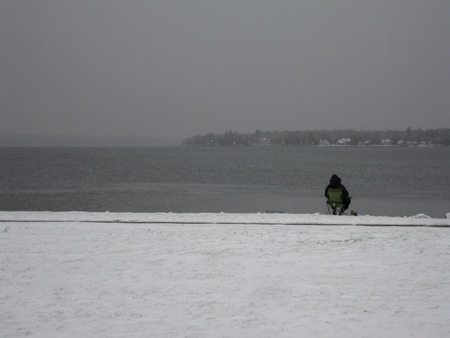 Patient winter fisherman tries his luck on a northern lake