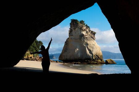 Silhouette of a young traveler woman enjoying in the marvelous landscape of Cathedral cove, Coromandel Peninsula Imagens