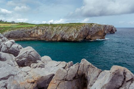 Line of rocks leading a view of a cliff in a cloudy day, location Bufones de Pria, Asturias, Spain