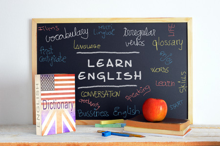 languages: Pizarra en una clase de Inglés. Algunos libros y material escolar para el estudio de idioma Inglés en un salón de clases.
