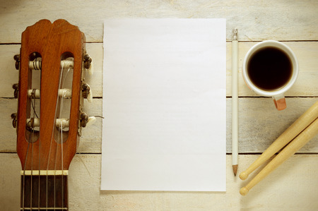 Inspirational background with a Spanish classical guitar on a wooden table while composing. Score sheet a pencil and a cup of coffee for the music composer 版權商用圖片