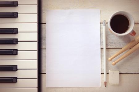 Inspirerende achtergrond met een piano op een houten tafel, terwijl het componeren. Scoreblad, een potlood en een kopje koffie voor de componist, Bovenaanzicht en een kopie ruimte voor tekst editor.