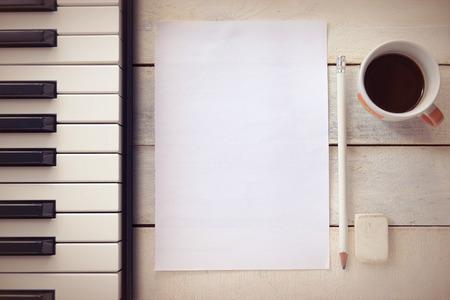 hoja en blanco: Fondo inspirada con un piano en una mesa de madera mientras redacta. Puntuaci�n de hoja, un l�piz y una taza de caf� para el compositor de la m�sica, vista superior y una copia espacio para el texto del editor.
